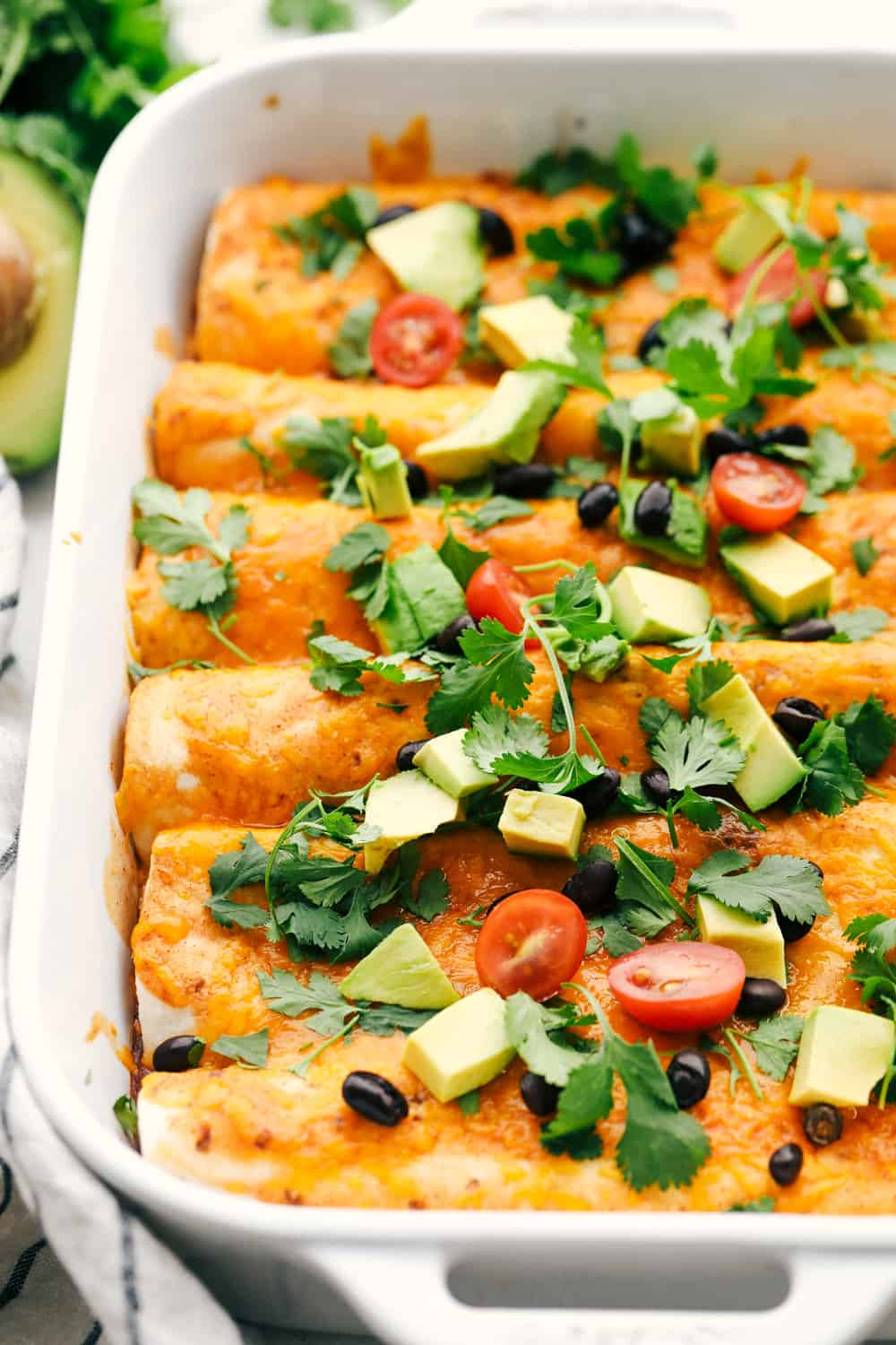 Sweet potato and black bean enchiladas cooked in a white dish with avocado and tomatoes.