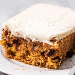 A carrot cake bar on a plate with a fork.