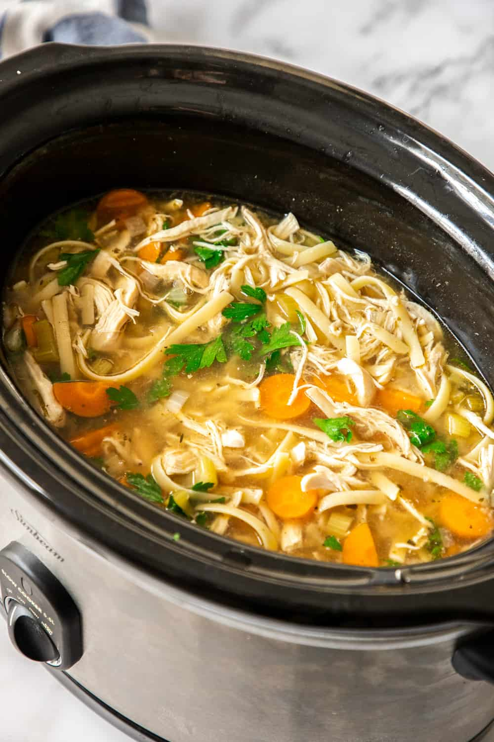 chicken noodle soup in the black bowl of a slow cooker
