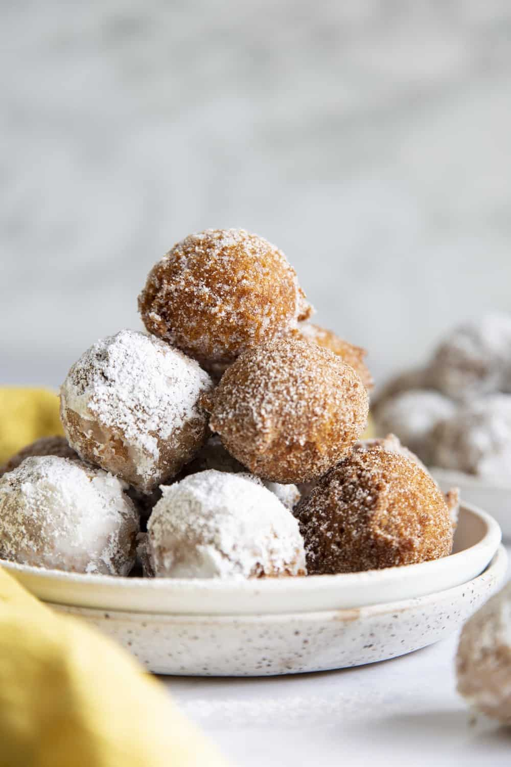 A plate full of powdered sugared and cinnamon sugared donut holes.