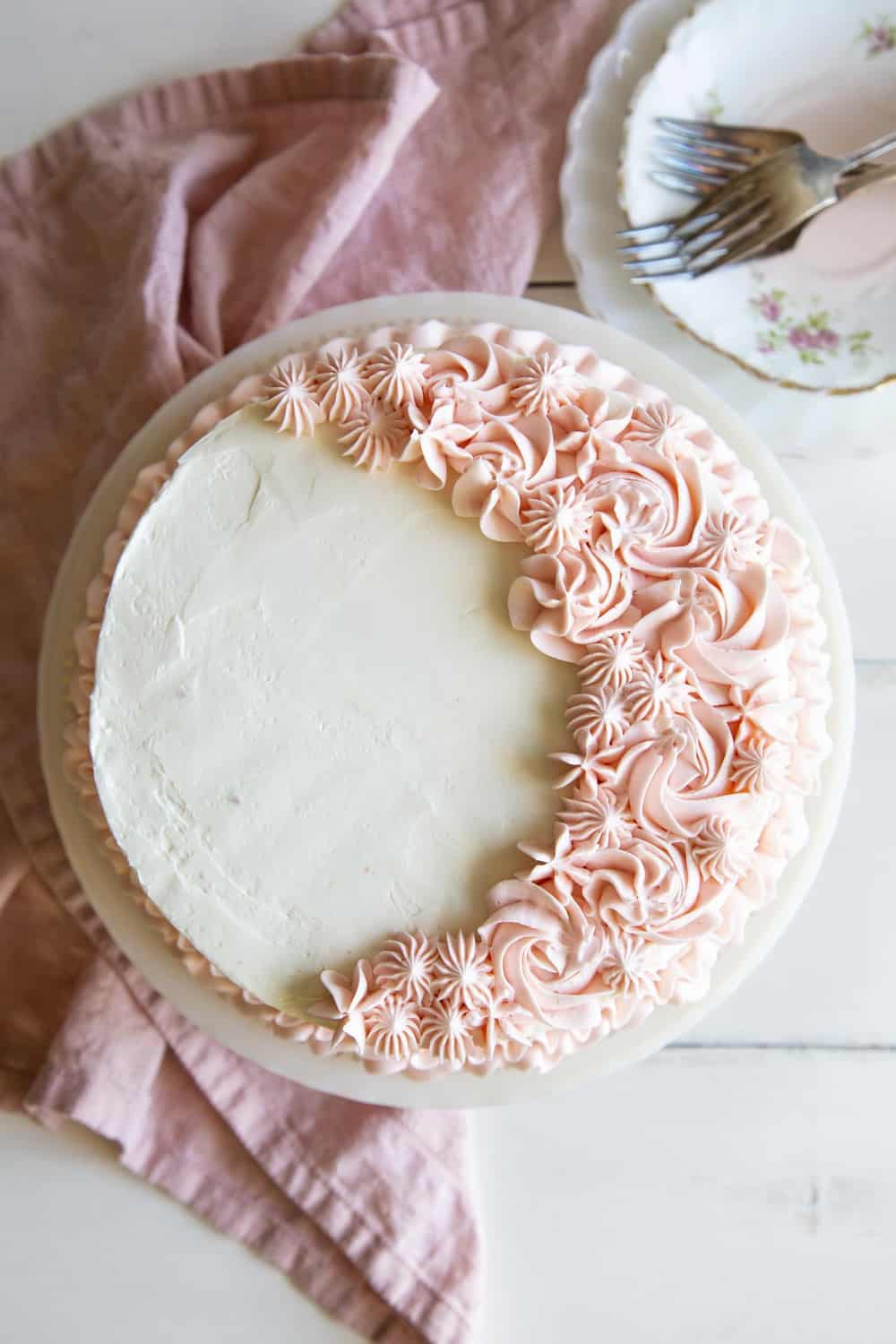 Pink velvet cake with white frosting and pink flowers.