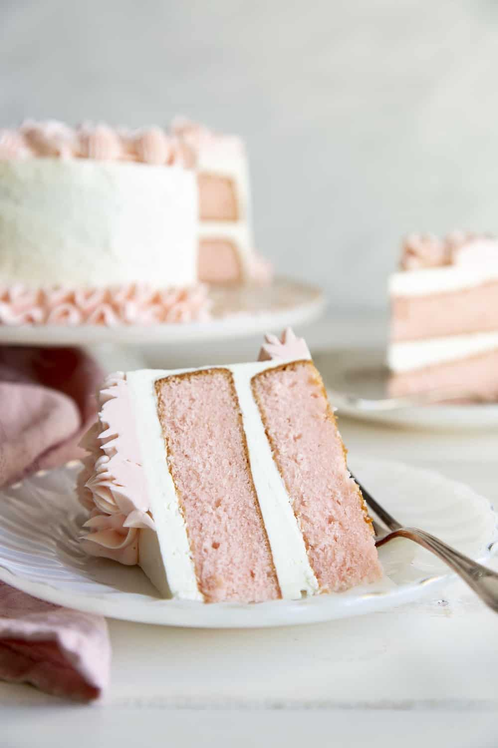 Pink fluffy velvet cake with white frosting and pink swirls on a plate with a fork.