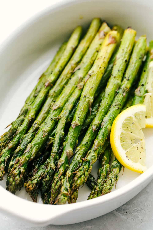 Air fryer memanggang asparagus di piring putih.