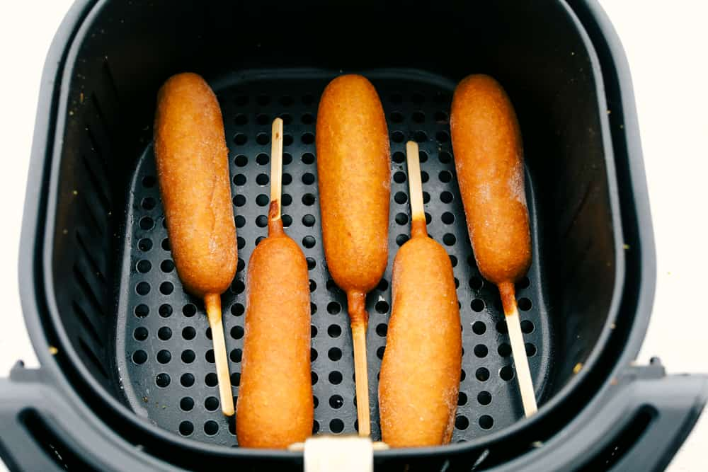 Corn dogs in the air fryer basket.