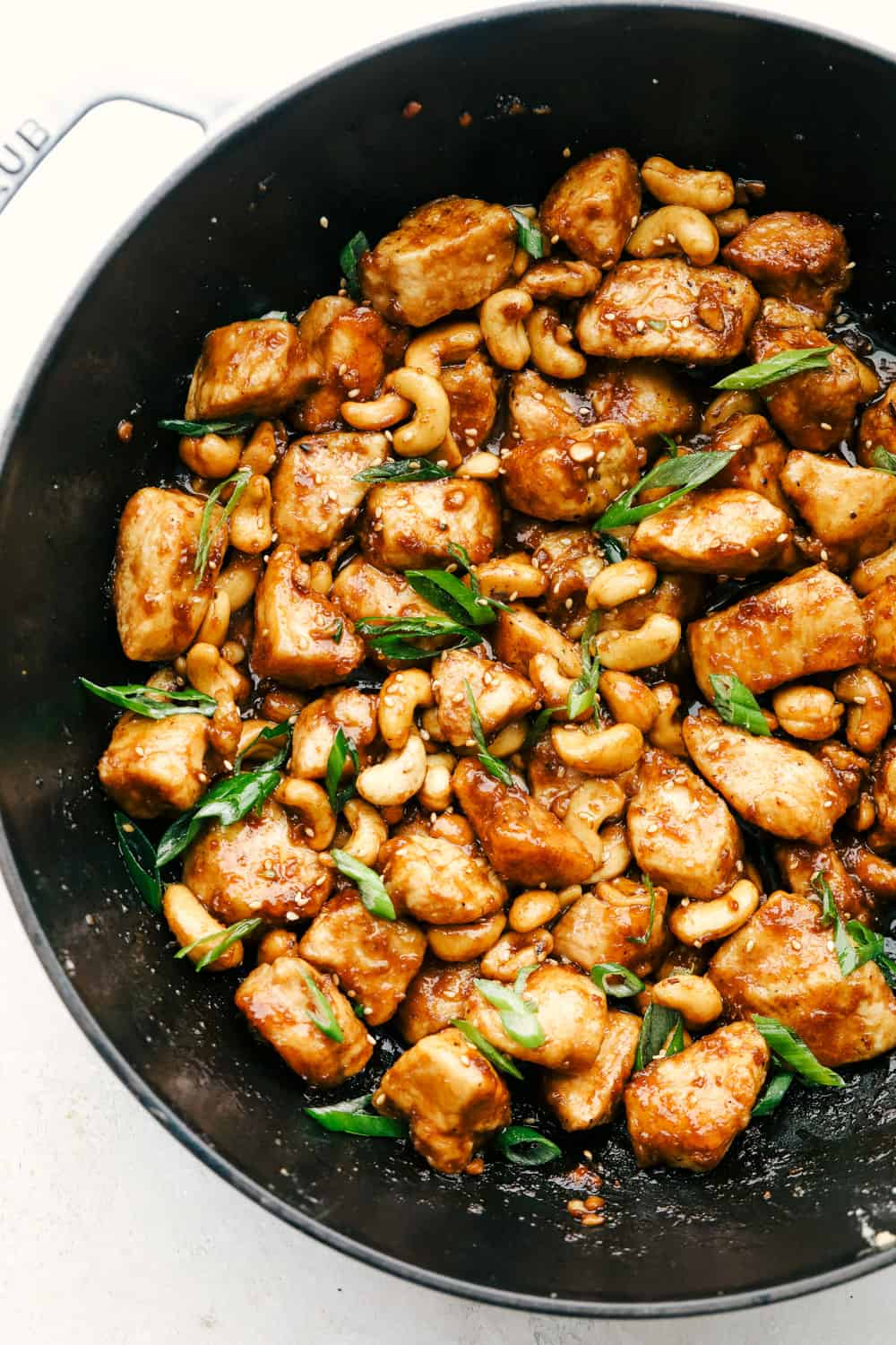 Cashew chicken in a wok with garnish.
