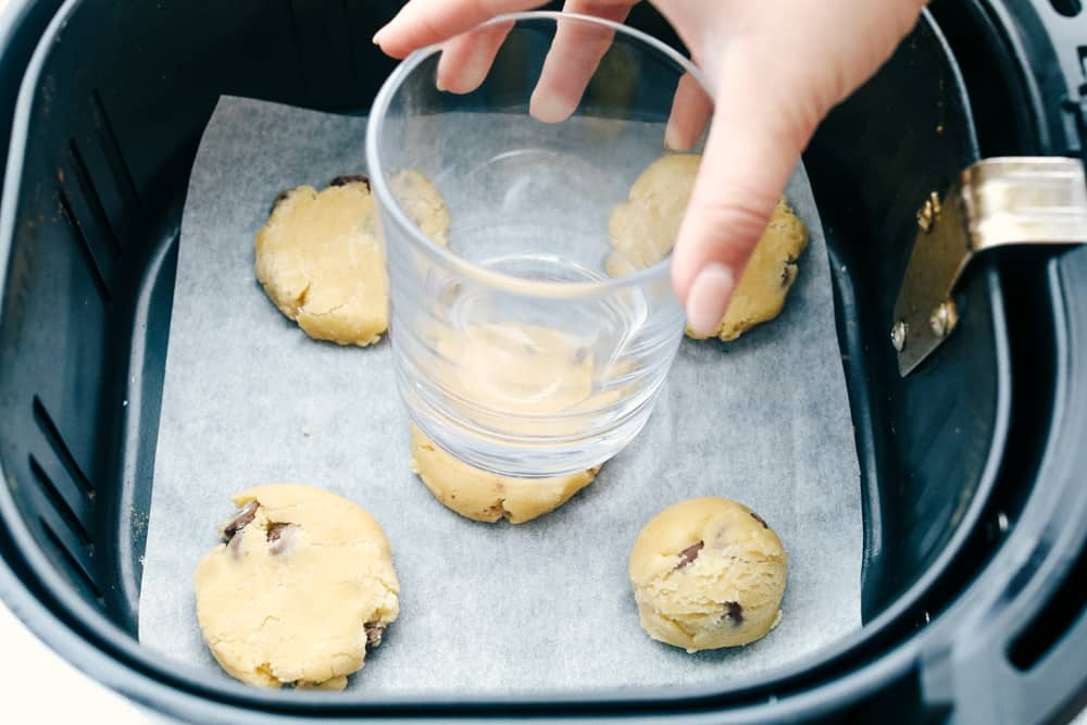 Flattening the cookies in the air fryer with a glass.