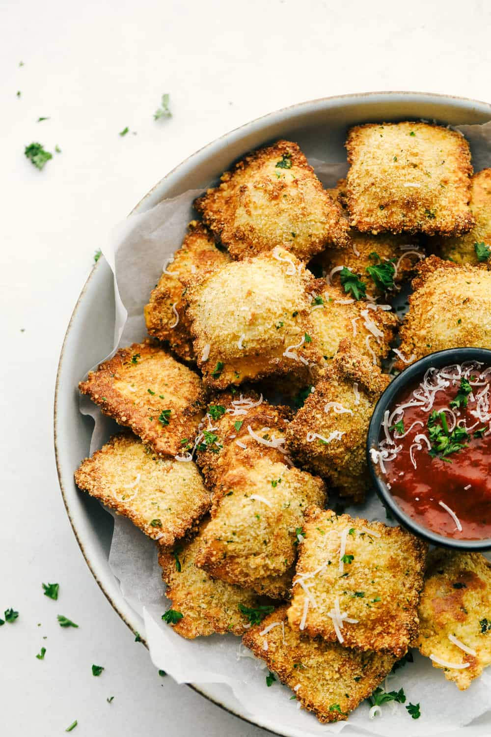 Toasted air fryer ravioli in a bowl with marinara.