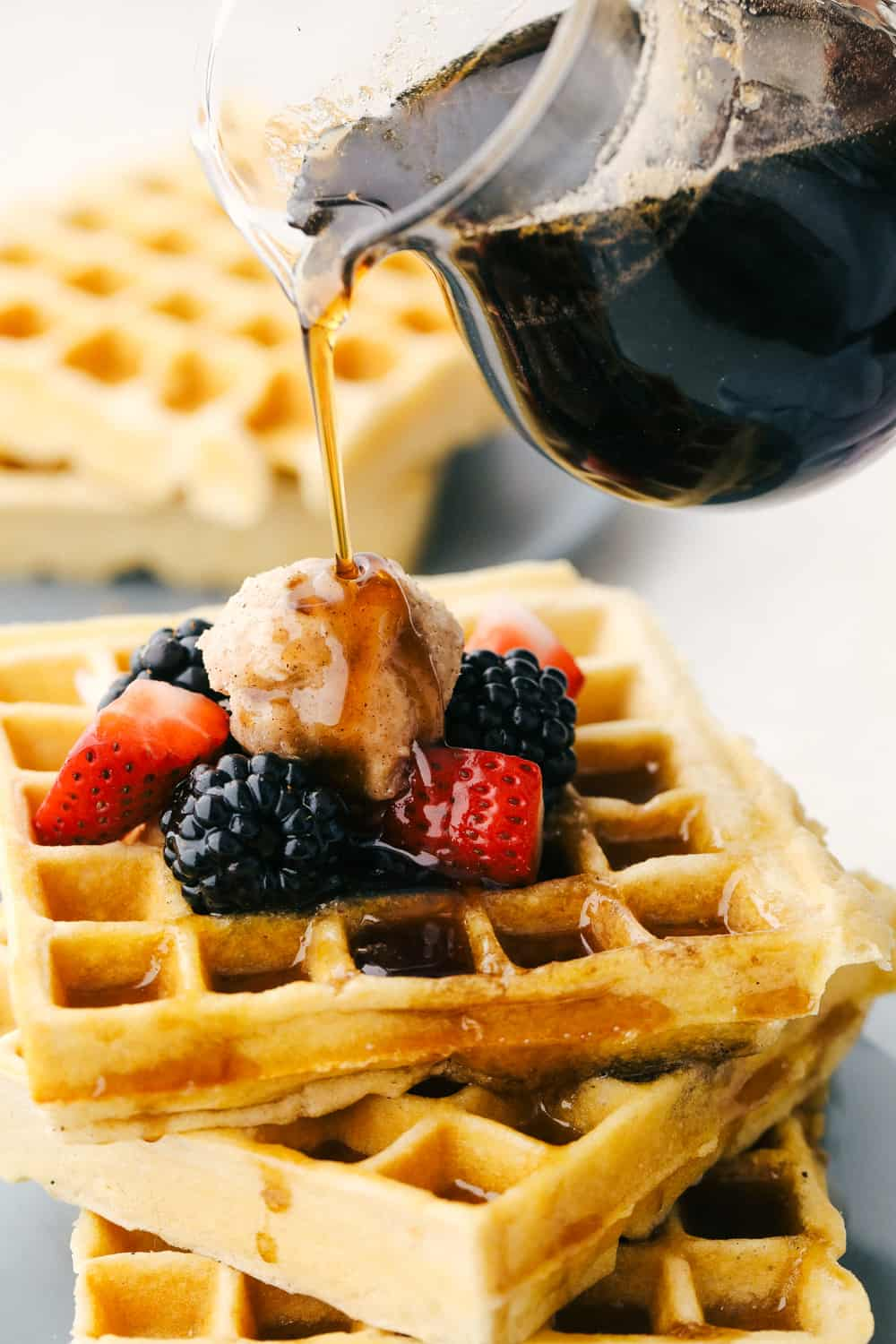Pouring maple syrup over waffles.