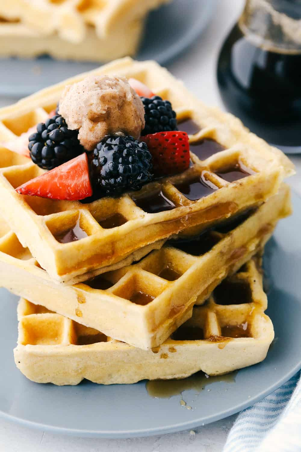 A Stack of fluffy waffles with fruit and syrup on a plate.