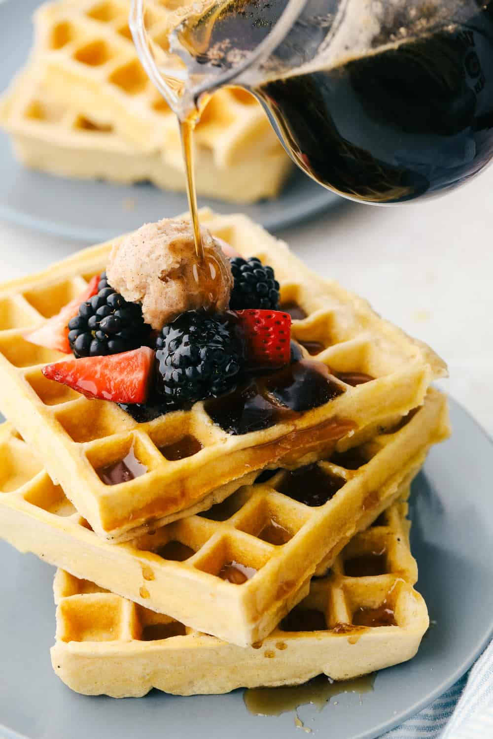 Drizzling syrup on top of a stack of homemade waffles.