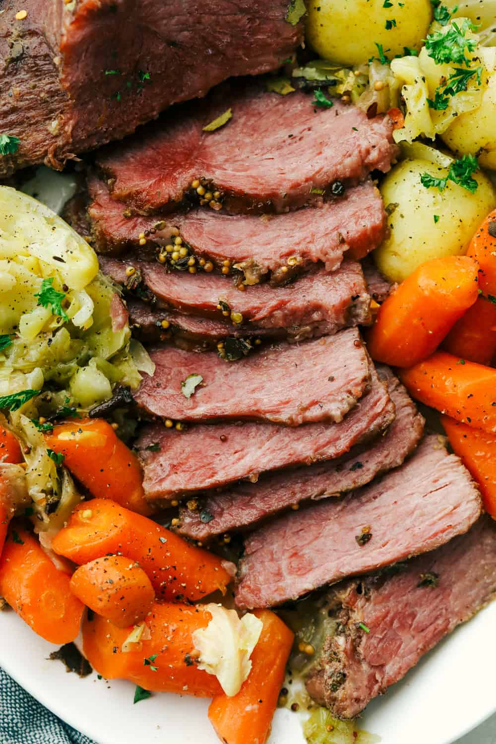 Sliced corned beef, cabbage, carrots, and potatoes on a plate.