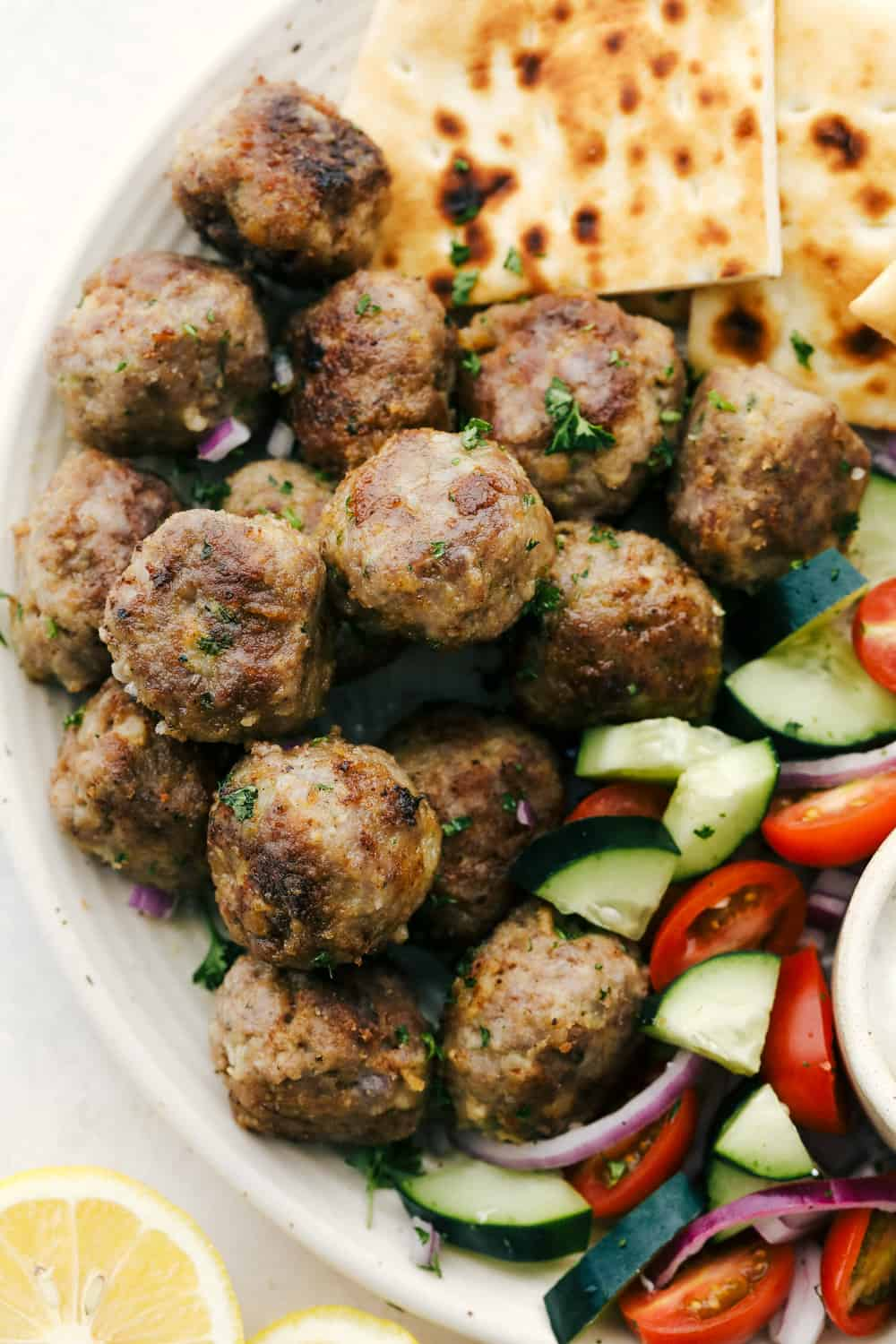 Browned meatballs on a platter with pitas and vegetables.