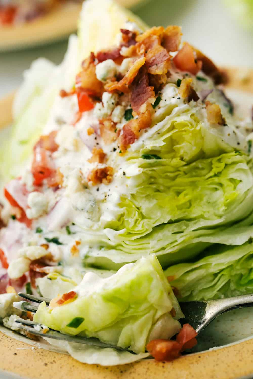 Up close picture of a wedge salad on a plate with a fork.