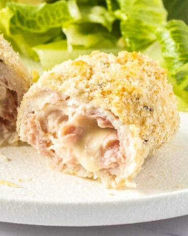 Closeup of the inside of chicken cordon blue with cheese oozing out.