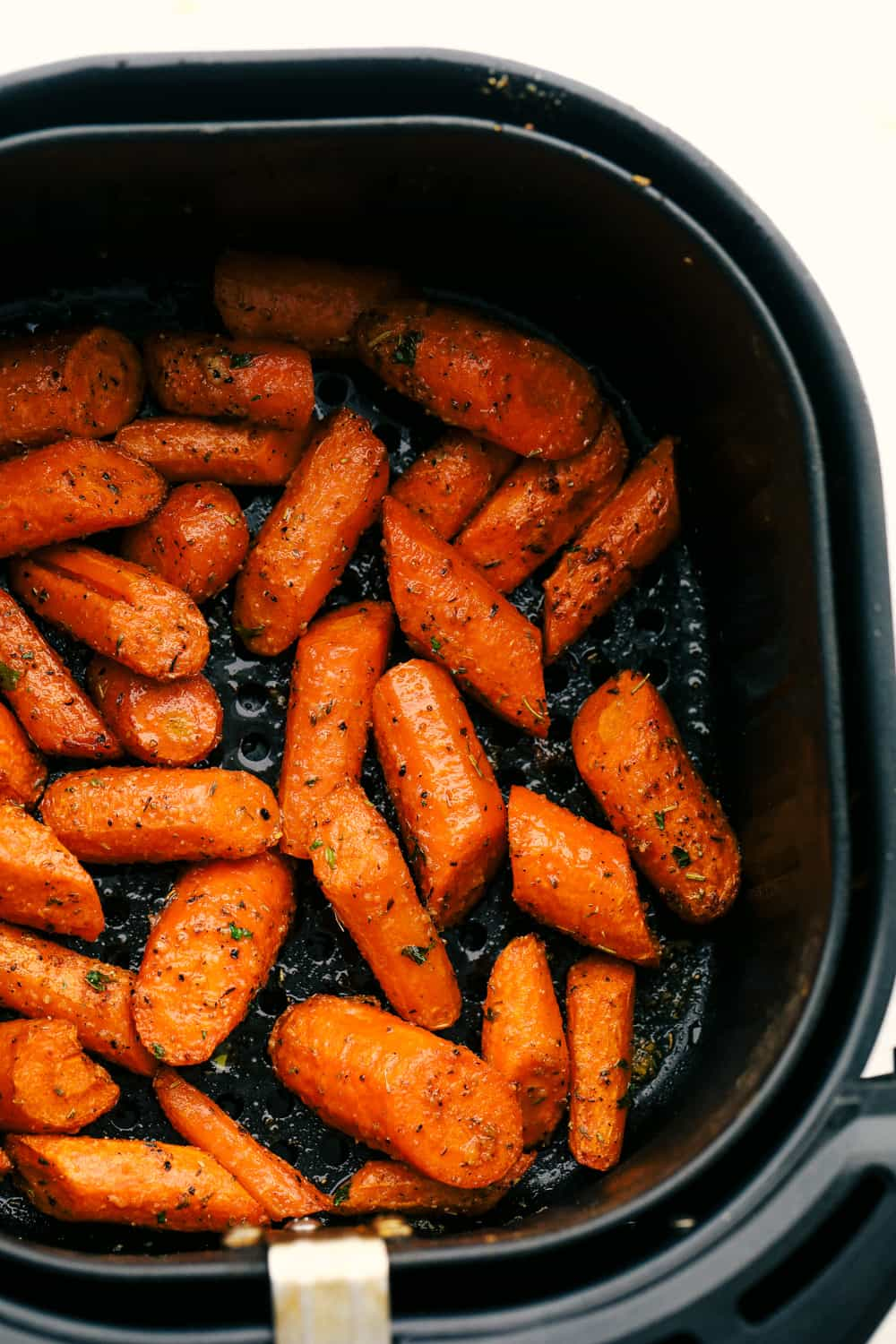Air fryer carrots seasoned in air fryer basket.