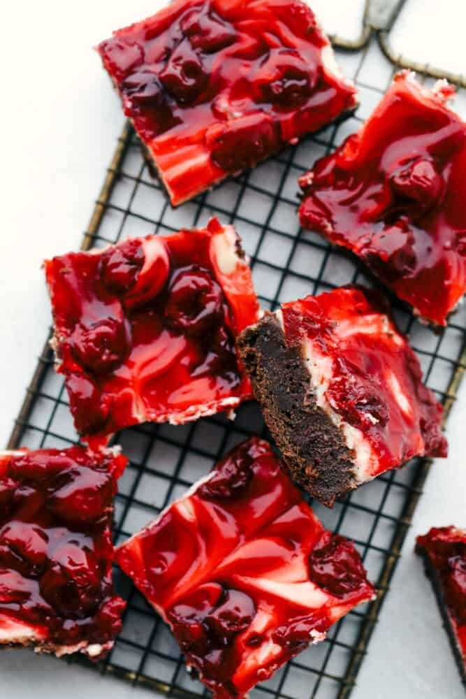 Sliced Cherry cheesecake brownies on  a cooling rack.
