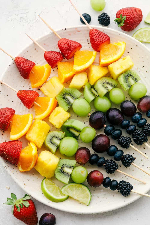 Rainbow fruit skewers on a plate.