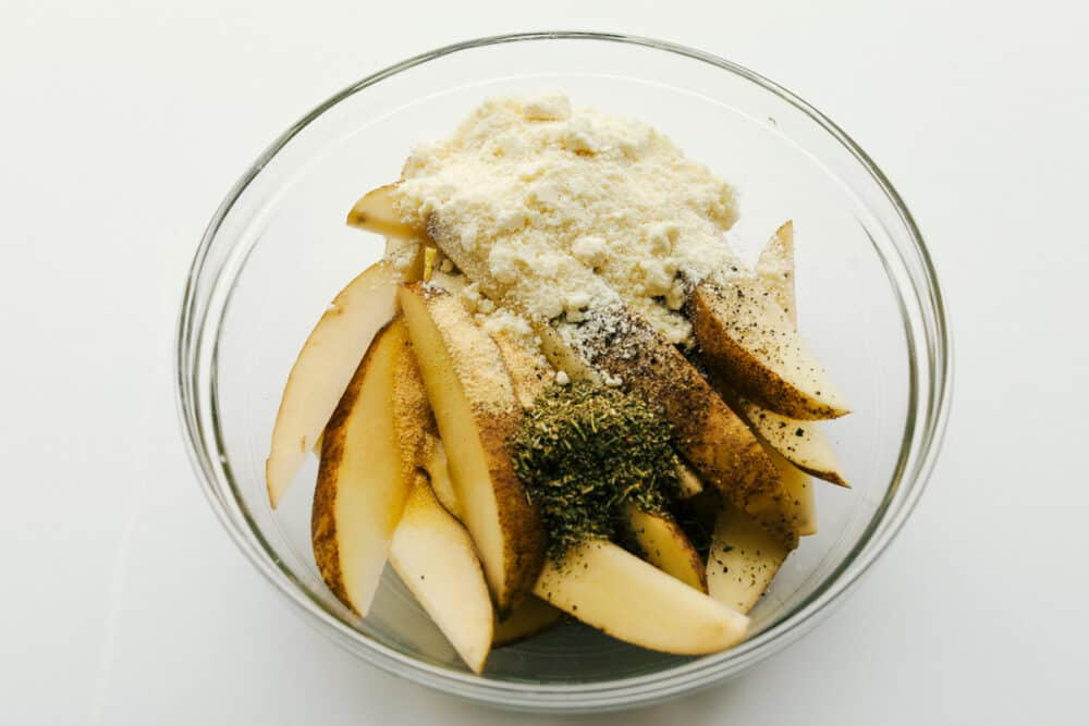 Potato wedges in a bowl with seasonings.