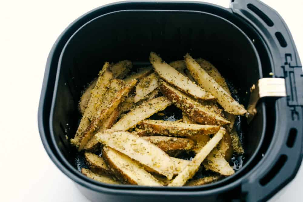 Air fryer basket full of wedges ready to cook.