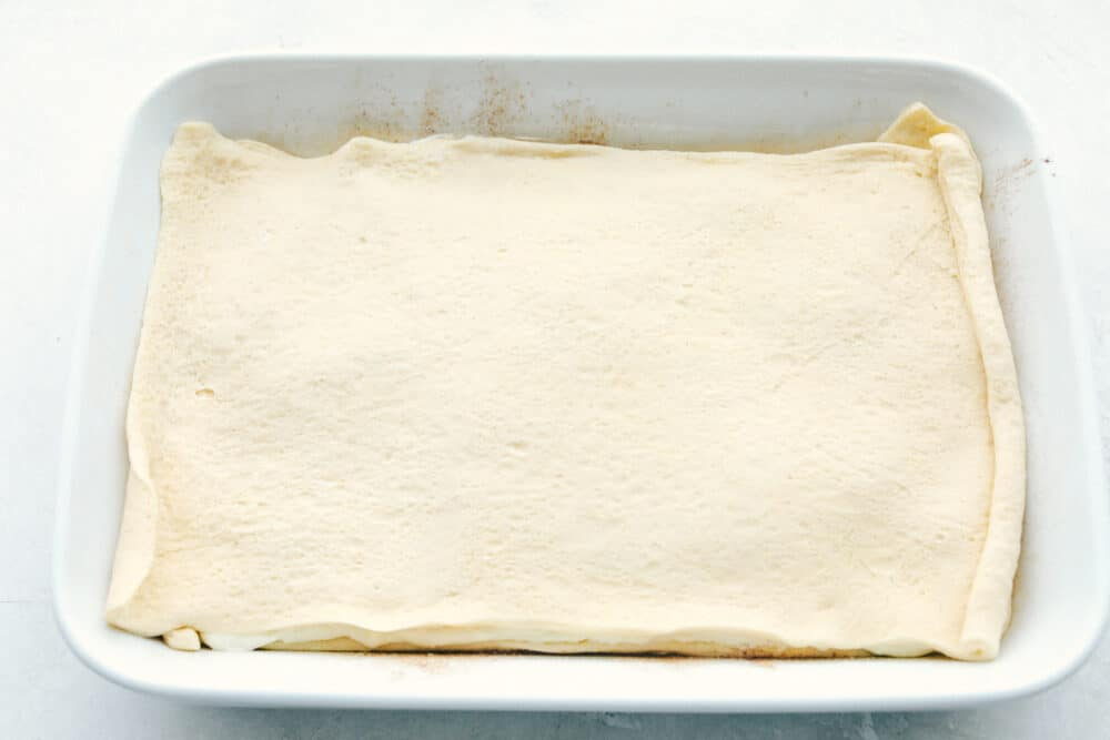 Layering the second sheet of cresent rolls over the cream cheese layer.