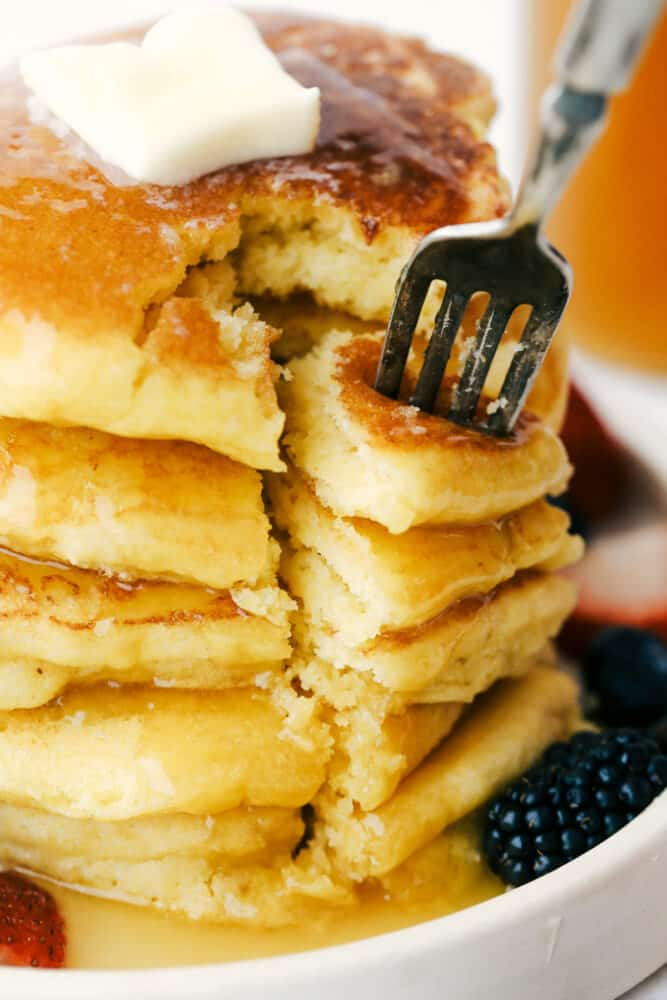 Using a fork to take a bite out of the stack of cornmeal pancakes.
