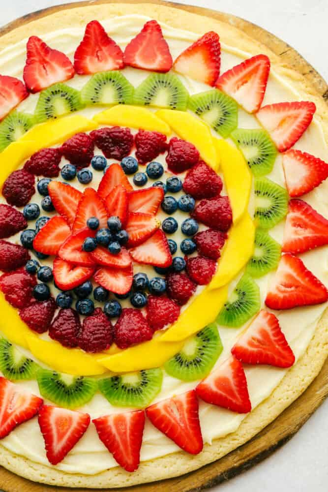 Fruit pizza with fresh fruit cut up and frosting underneath.