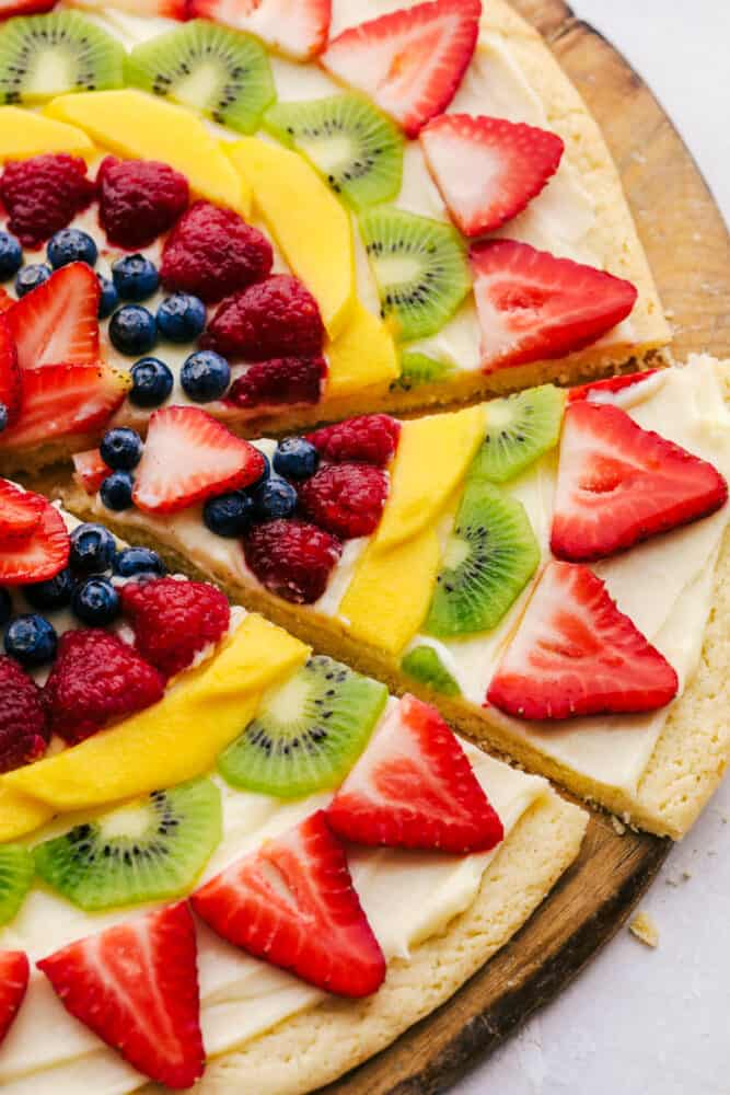 Taking a slice of fruit pizza.