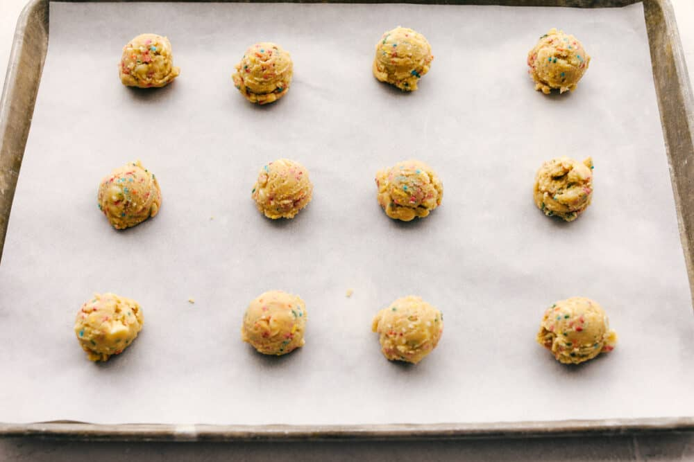 Formed cookie dough balls on a parchment lined cookie sheet.