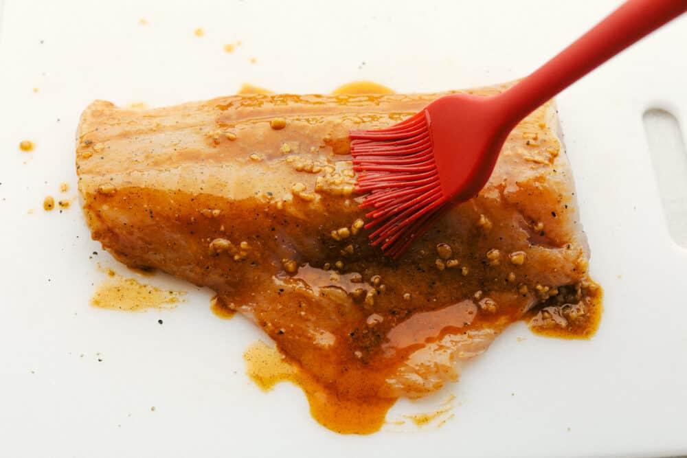 Bedruip de kabeljauw met de cajun-knoflookkruiden.