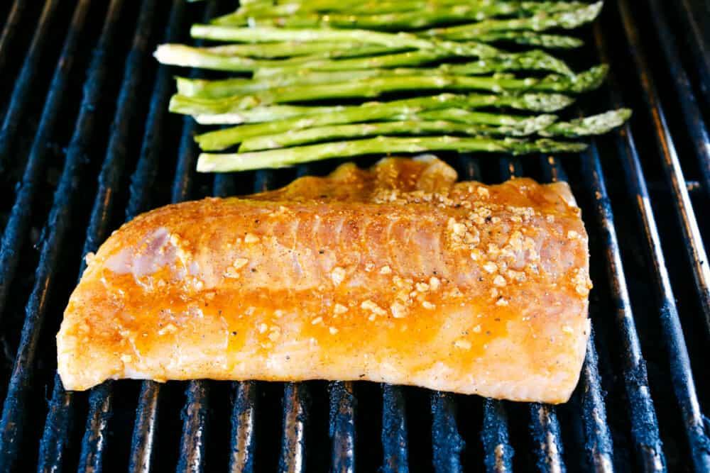 Kabeljauw en asperges op de grill koken.