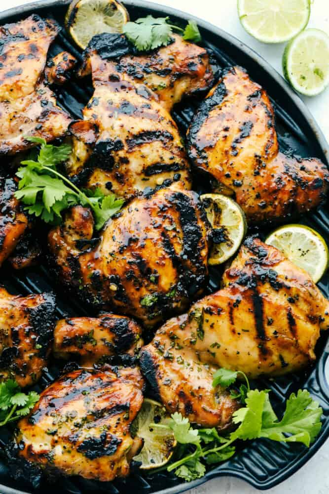 A plate of grilled honey lime cilantro chicken garnished with cilantro and limes.