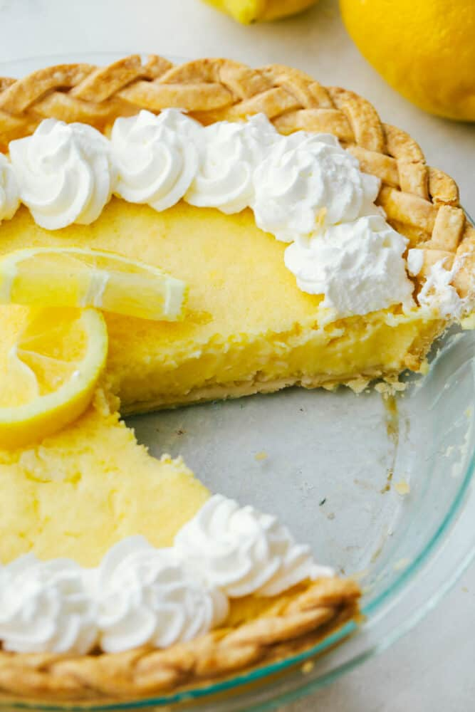 A slice missing from a fresh lemon pie.