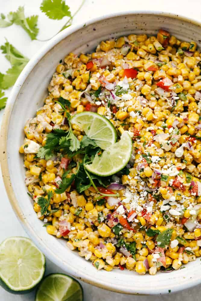 Mexican Corn Salad garnished with limes and cilantro.