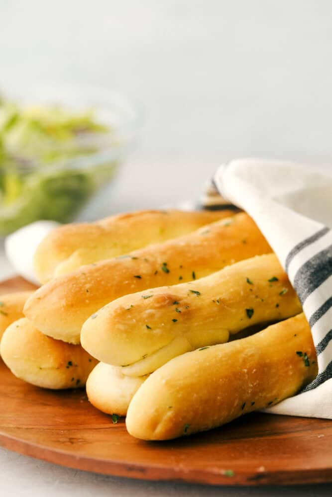 A bunch of breadsticks wrapped in a towel ready to eat.