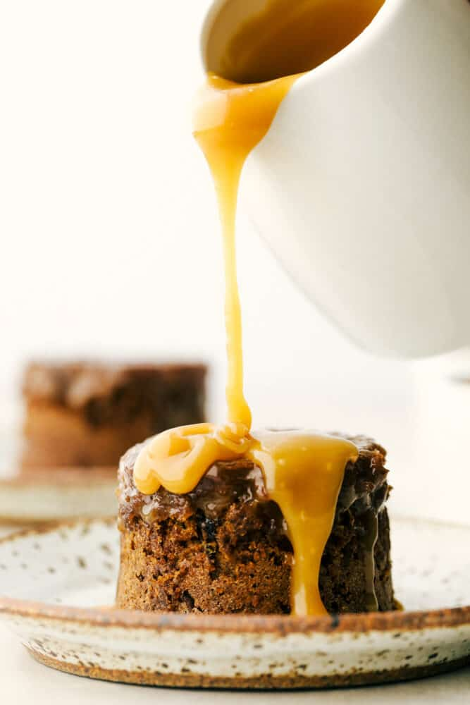 Pouring toffee sauce over the sticky pudding.