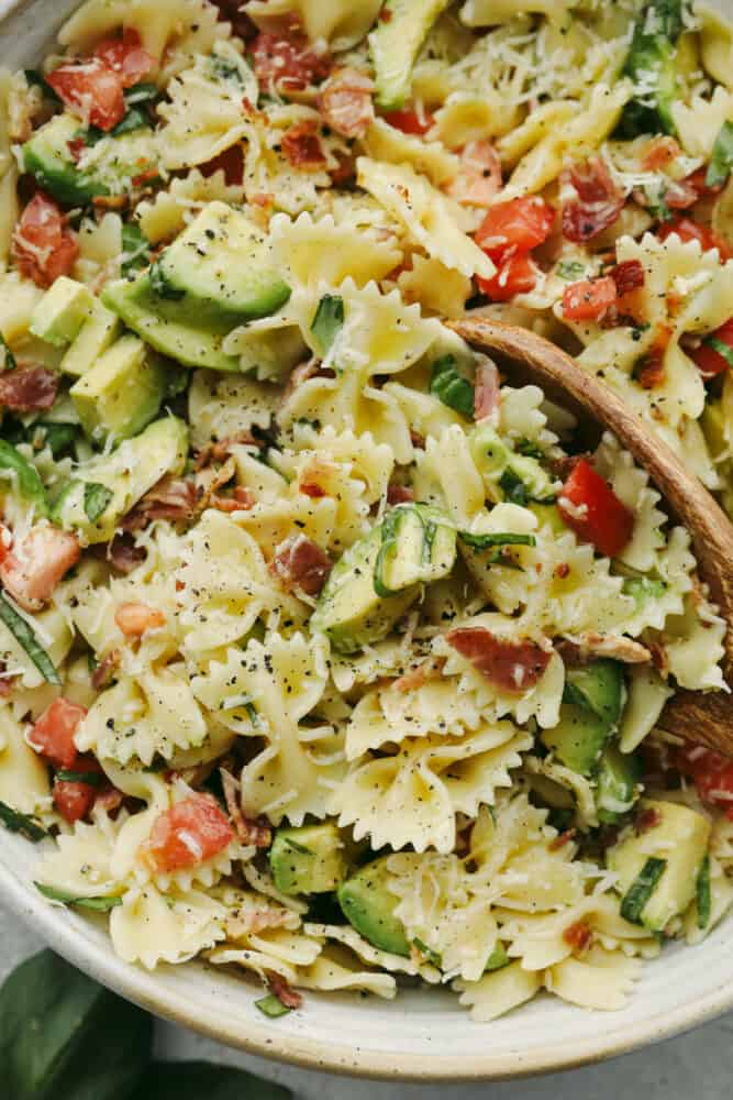 Up close pasta salad with a wooden spoon.