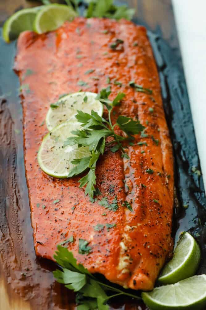 Salmon panggang di atas papan kayu cedar dengan hiasan jeruk nipis.