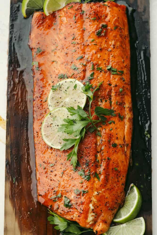 Salmon panggang di atas cedar plank dengan hiasan.