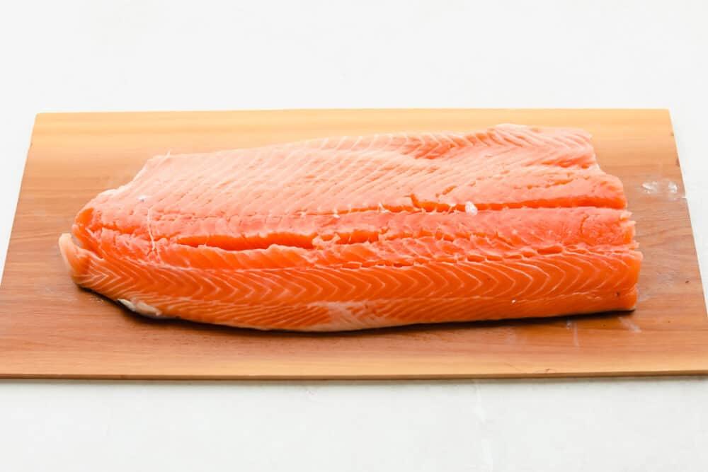 Potongan salmon segar di atas papan cedar.