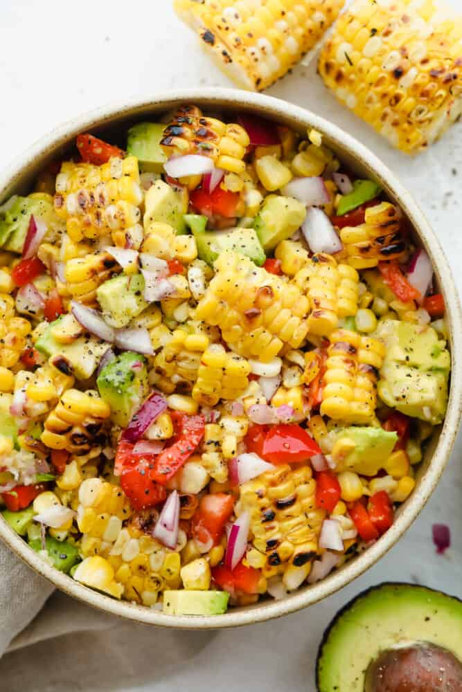 A bowl full of summer corn salad ready to eat.
