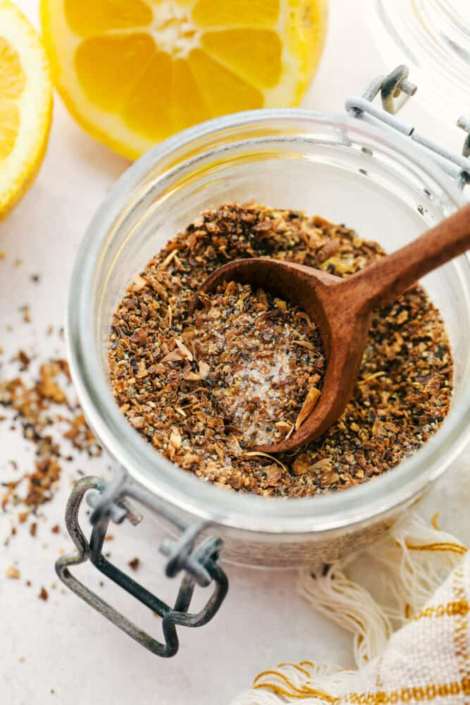 Lemon pepper in a glass jar with a wooden spoon.