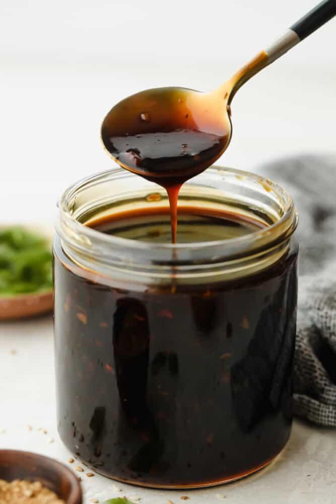 Spooning teriyaki sauce out of jar.