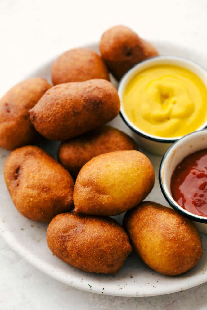 Mini corn dogs on a plate with mustard and ketchup on the side.
