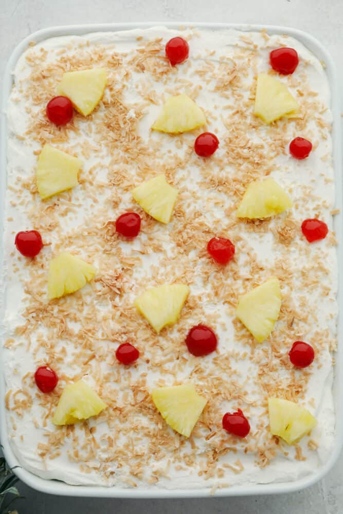 Decorated pina colada poke cake with pineapple, and maraschino cherries.