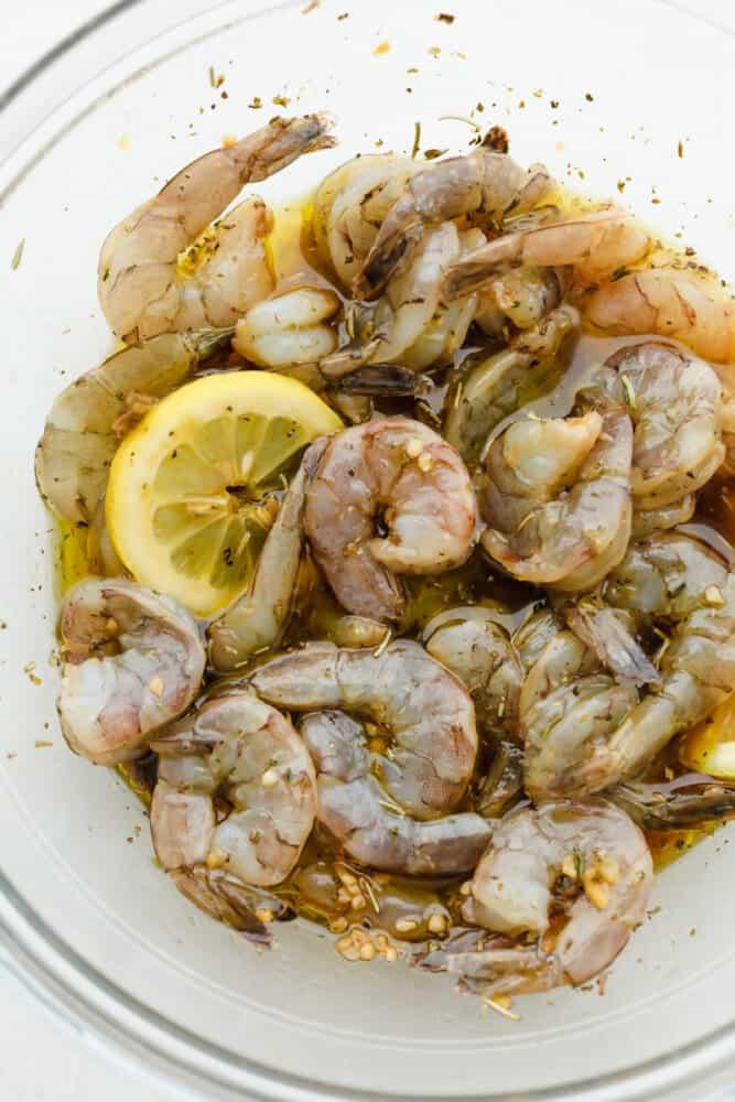 Fresh shrimp in marinade with lemon slices.