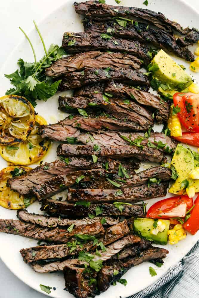 Skirt steak grilled and sliced on a white plate.