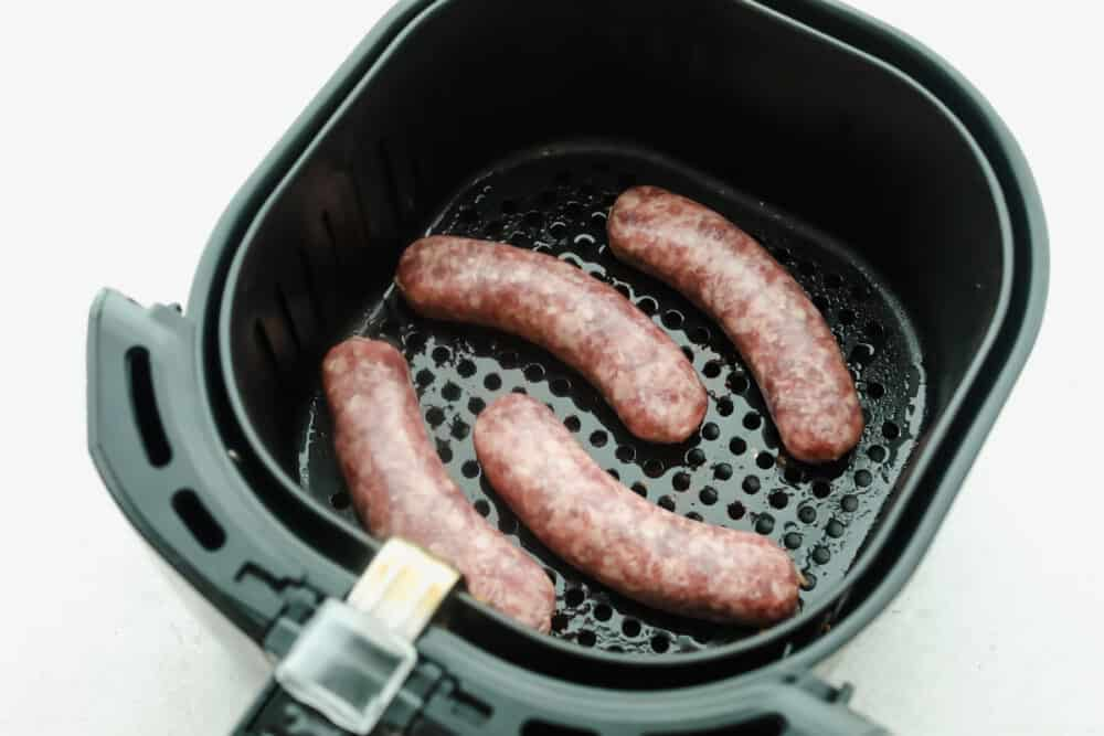 Brats in the air fryer basket ready to cook.