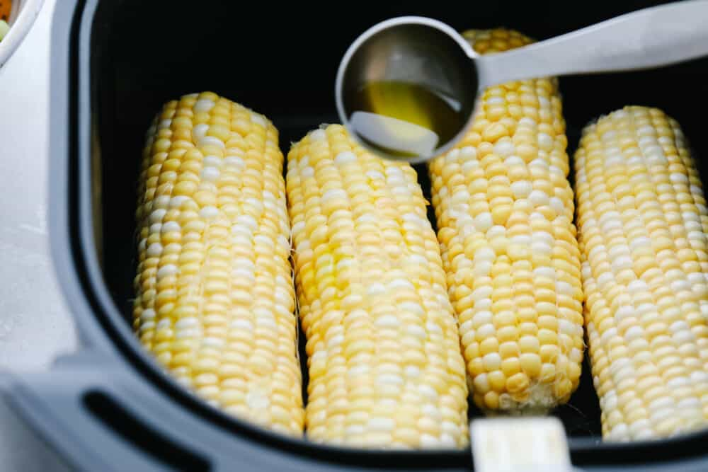 Drizzling the corn with olive oil before air frying.