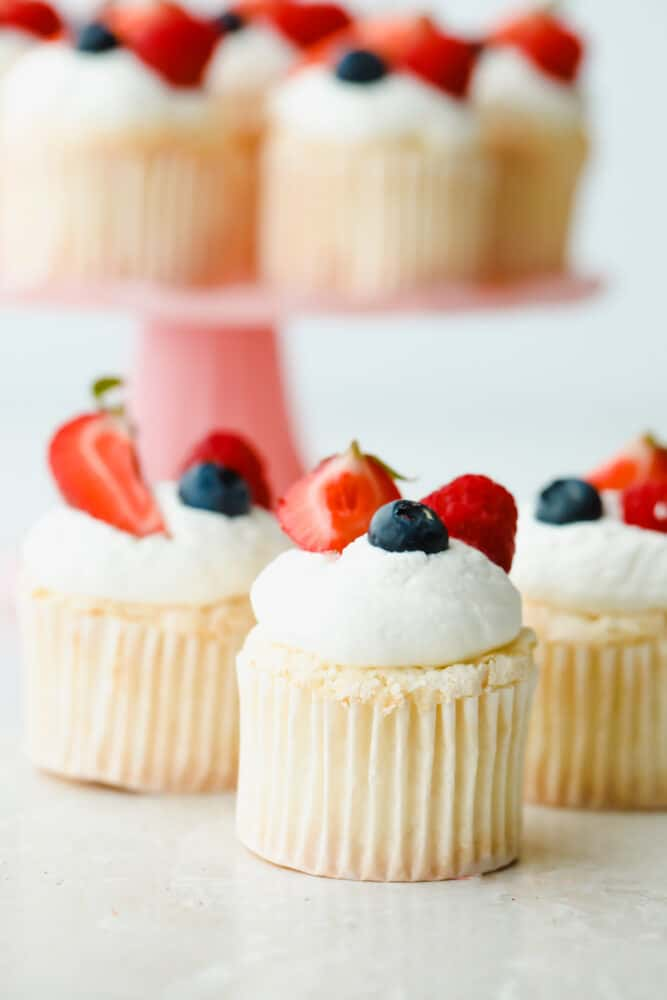 Angel Food Cupcakes topped with blueberries and strawberries.