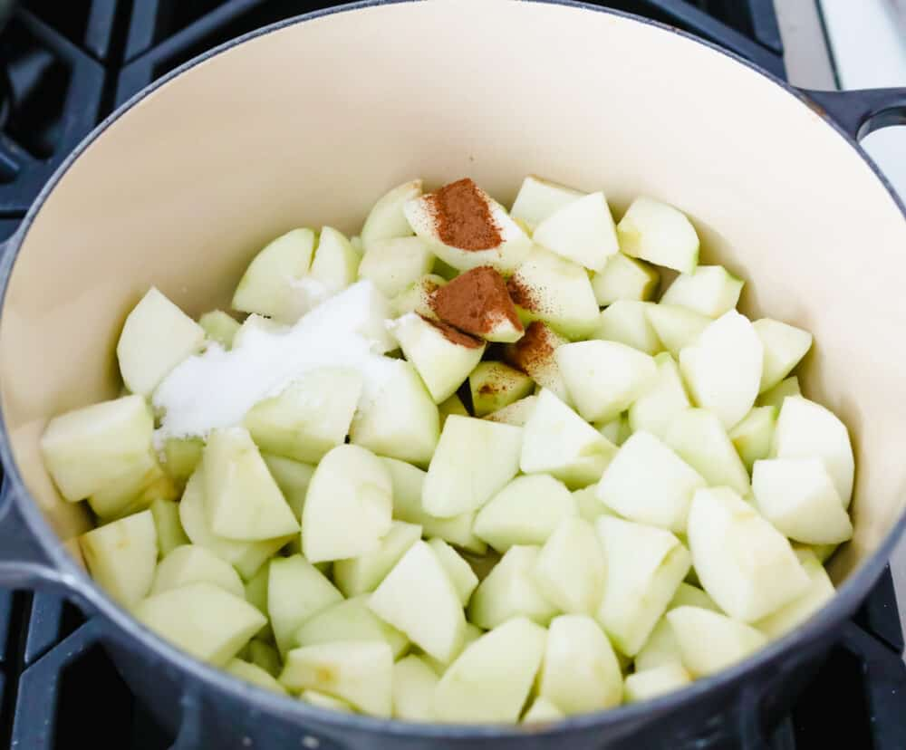 Chopped apples in a bowl with sugar and cinnamon being added as ingredients.